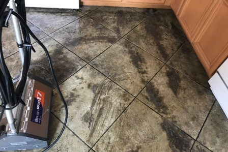 Hand of man wearing orange rubber gloves is used to convert scrub cleaning on the tile floor