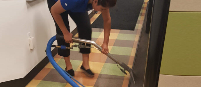 A Janitor Cleaning Carpet With Vacuum