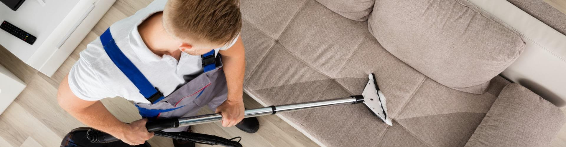 man cleaning the couch using vacuum cleaner